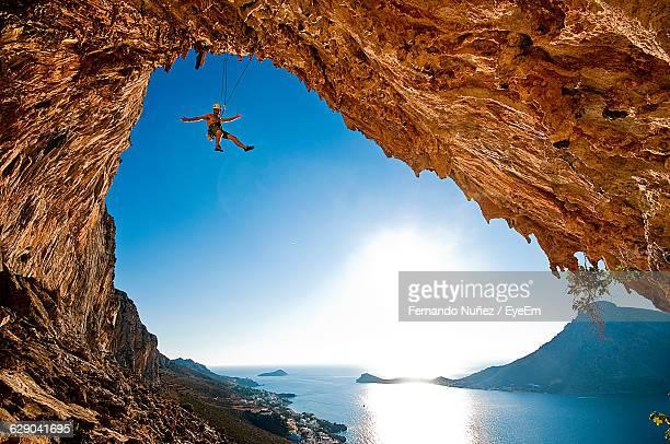 low angle view of man climbing rock by lake against sky - exhilaration stock photos and pictures