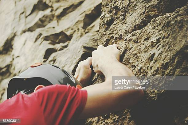 low angle view of man climbing rock - caley chase stock photos and pictures