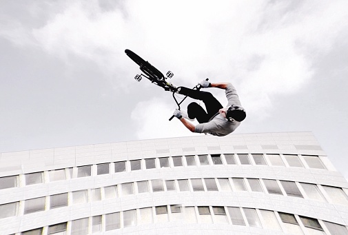 Low Angle View Of Man Doing Stunt With Bicycle By Building Against Sky - gettyimageskorea