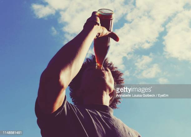 low angle view of man drinking cola against sky - rafraîchissement photos et images de collection