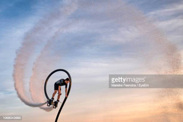 low angle view of man flyboarding against sky - エクストリームスポーツ ストックフォトと画像