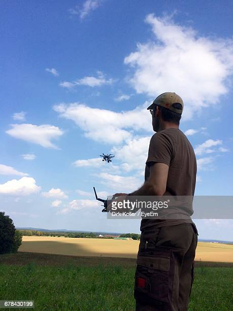 low angle view of man flying drone over field - low flying aircraft stock pictures, royalty-free photos & images