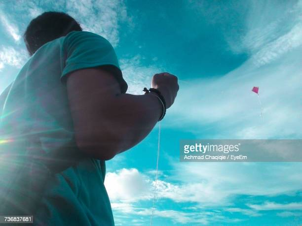 Low Angle View Of Man Flying Kite In Blue Sky