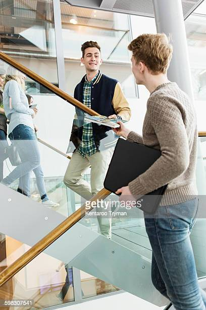 Low angle view of man giving book to friend in university