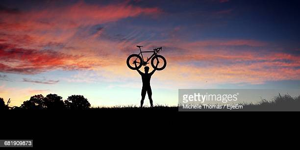 Low Angle View Of Man Holding Bicycle Above Head Against Sunset