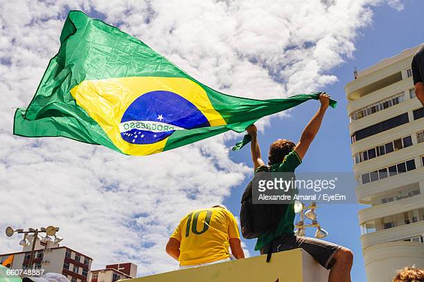 Low Angle View Of Man Holding Brazilian Flag By Friend Against Buildings On Sunny Day