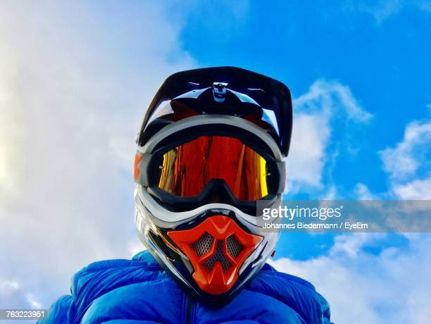 Low Angle View Of Man In Helmet Against Blue Sky