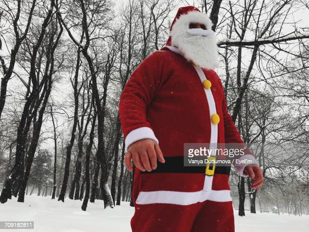 Low Angle View Of Man In Santa Costume Standing On Snow Covered Field