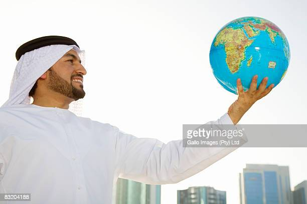 Low angle view of man in traditionally Middle Eastern attire holding globe, Dubai cityscape in background, UAE