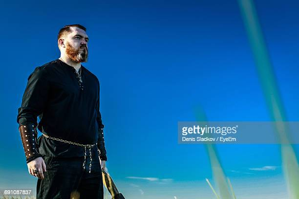 Low Angle View Of Man In Viking Costume Against Clear Blue Sky