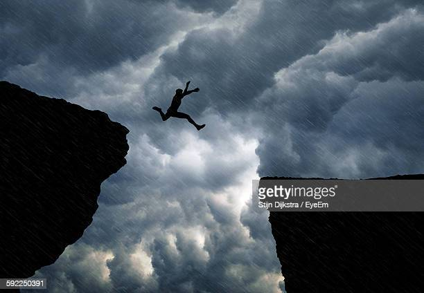 low angle view of man jumping from cliff against cloudy sky - 崖 ストックフォトと画像