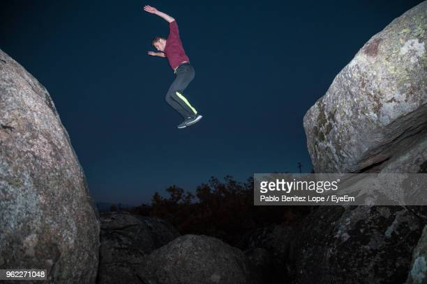 Low Angle View Of Man Jumping On Rock At Night