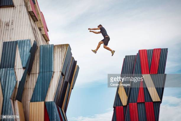 low angle view of man jumping over buildings against sky - acrobatic activity stock photos and pictures