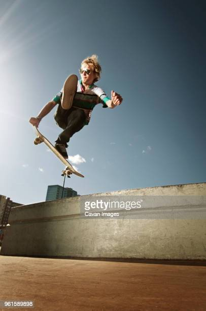 Low angle view of man jumping with skateboard against sky