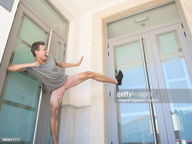Low Angle View Of Man Kicking Door