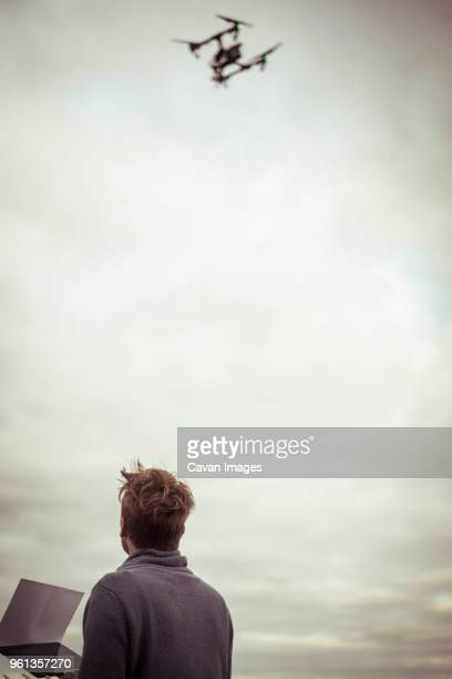 low angle view of man looking at and operating drone - low flying aircraft stock pictures, royalty-free photos & images