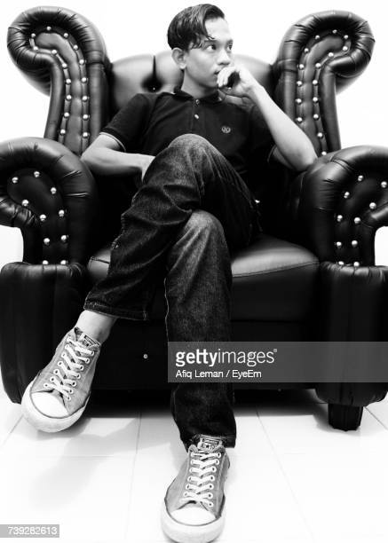 Low Angle View Of Man Looking Away While Sitting On Armchair At Home