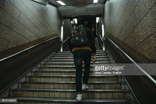 Low Angle View Of Man Moving Up On Staircase At Subway Station