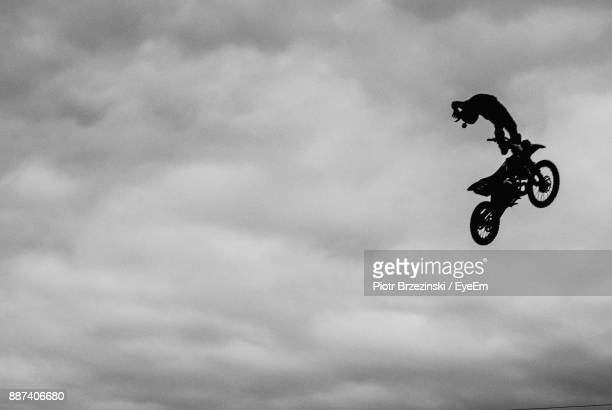 low angle view of man on motorcycle in mid-air against cloudy sky - stunt person stock photos and pictures