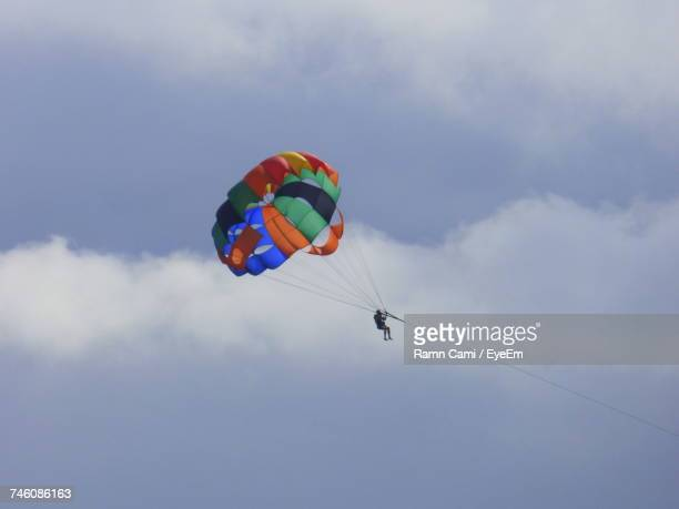Low Angle View Of Man Parasailing Against Cloudy Sky