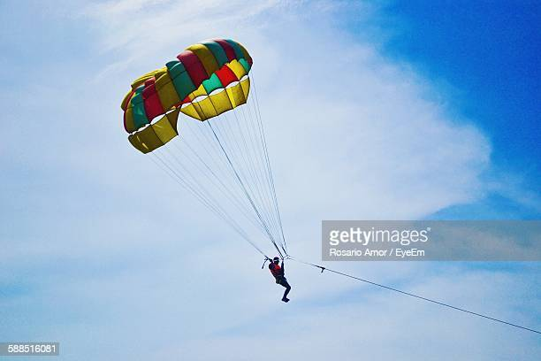 Low Angle View Of Man Parasailing In Cloudy Sky