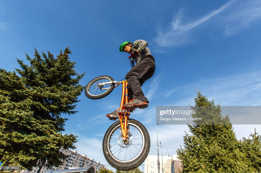 Low Angle View Of Man Performing Bicycle Stunt Against Sky : Stock Photo