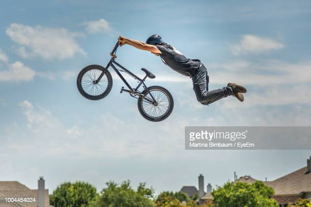 low angle view of man performing stunt on bicycle against sky - bmx cycling stock pictures, royalty-free photos & images