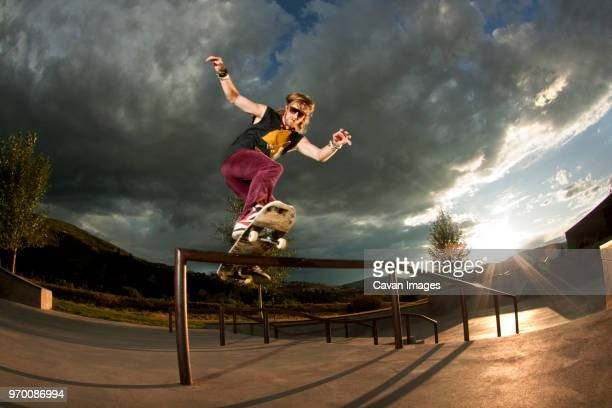 Low angle view of man performing stunt on sports ramp against cloudy sky
