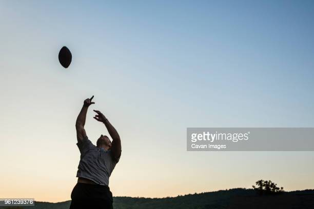 low angle view of man playing football against clear sky during sunset - ラグビーボール ストックフォトと画像