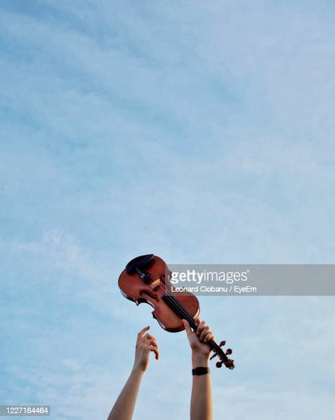 low angle view of man playing guitar against sky - classical musician stock pictures, royalty-free photos & images