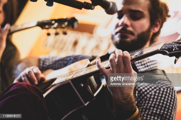 low angle view of man playing guitar - acoustic guitar stock pictures, royalty-free photos & images