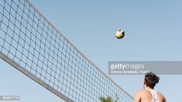 low angle view of man playing volleyball against clear sky - beach volleyball stock pictures, royalty-free photos & images