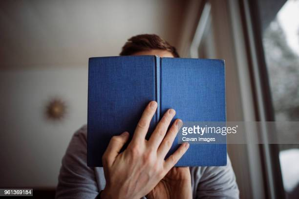 low angle view of man reading book while sitting at home - man holding book stock pictures, royalty-free photos & images