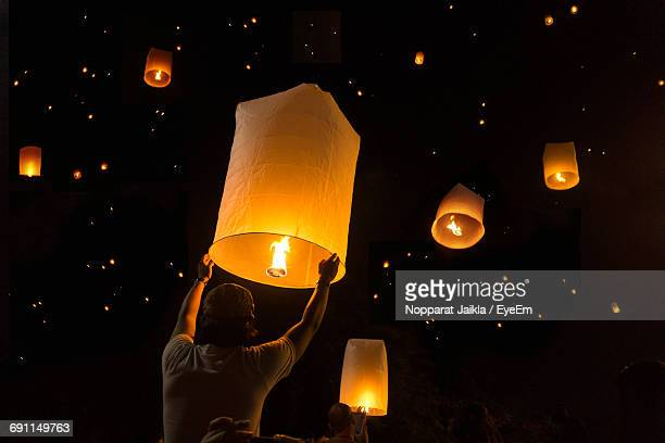 low angle view of man releasing paper lantern at night - releasing stock photos and pictures