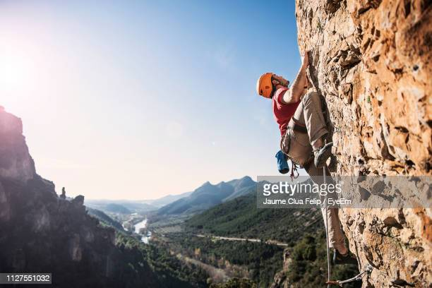 low angle view of man rock climbing against sky - rock climbing stock pictures, royalty-free photos & images