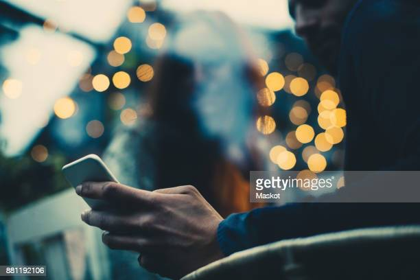 low angle view of man showing mobile phone to young female friend during dinner party - evening meal ストックフォトと画像