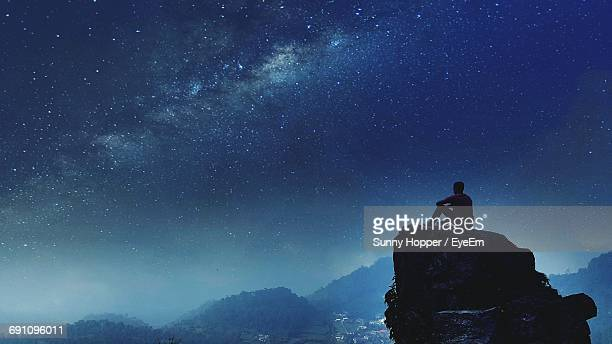 Low Angle View Of Man Sitting On Cliff Against Star Field