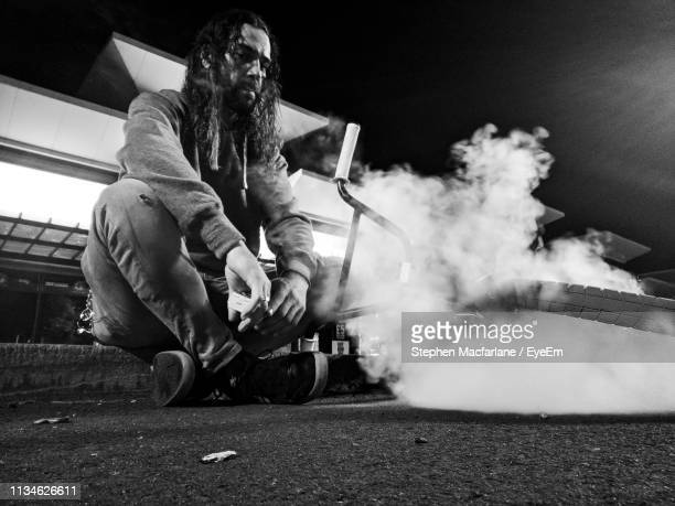 Low Angle View Of Man Sitting With Bicycle Amidst Smoke On Road At Night