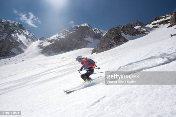 low angle view of man skiing on snow covered mountain - andrea rizzi foto e immagini stock