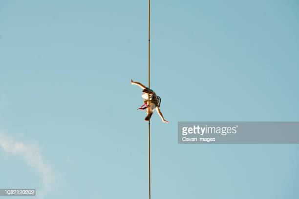 low angle view of man slacklining against clear blue sky during sunny day - coraggio foto e immagini stock