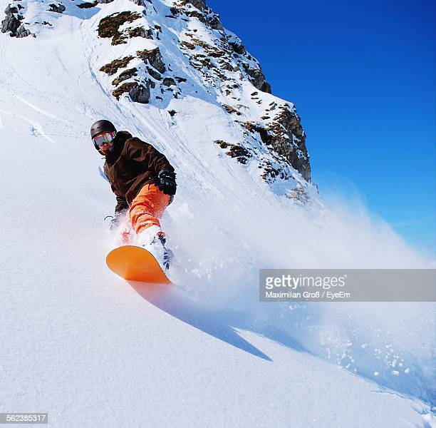 Low Angle View Of Man Snowboarding On Snowcapped Mountain