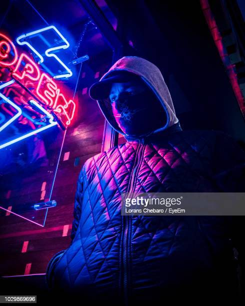 Low Angle View Of Man Standing By Illuminated Signboard At Night
