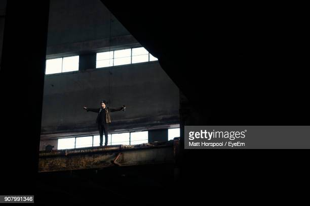 Low Angle View Of Man Standing In Abandoned Building