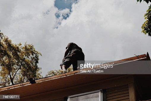 Low Angle View Of Man Standing On House Roof Against Sky