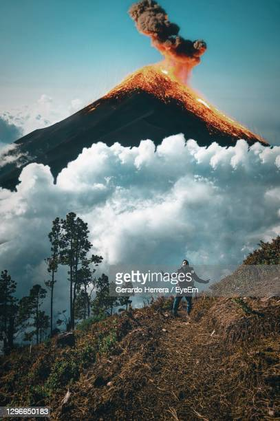 low angle view of man standing on land against an active volcano in guatemala - guatemala stock pictures, royalty-free photos & images
