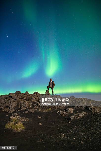 Low Angle View Of Man Standing On Mountain At Night