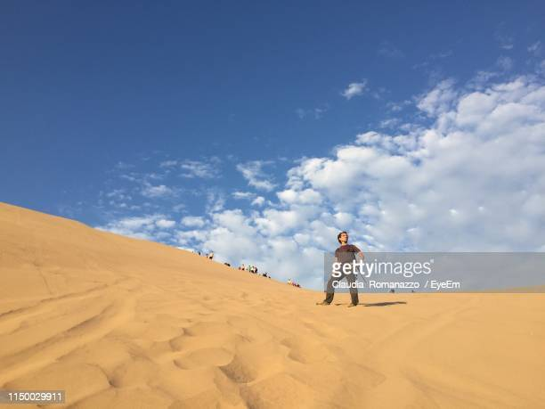 low angle view of man standing on sand dune in desert against sky - claudia romanazzo foto e immagini stock