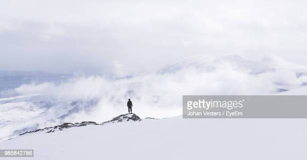 low angle view of man standing on snowcapped mountains against sky - extreme weather stock photos and pictures