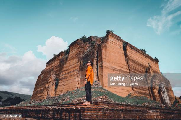 low angle view of man standing on temple against sky - myanmar stock pictures, royalty-free photos & images
