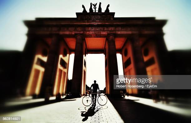 Low Angle View Of Man Standing With Bicycle In Front Of Brandenburg Gate